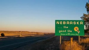 zoom-out-timelapse-view-of-roads-with-the-welcome-to-nebraska-sign-near-the-state-border_nhiyljzux__S0000